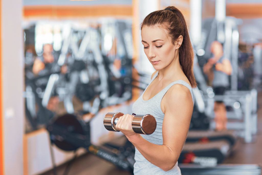 Strong woman weightlifting at the gym looking happy and working on her biceps