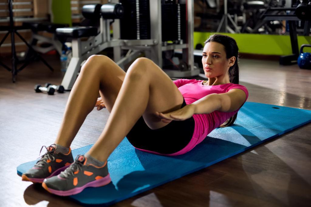 Woman doing sit-ups at gym