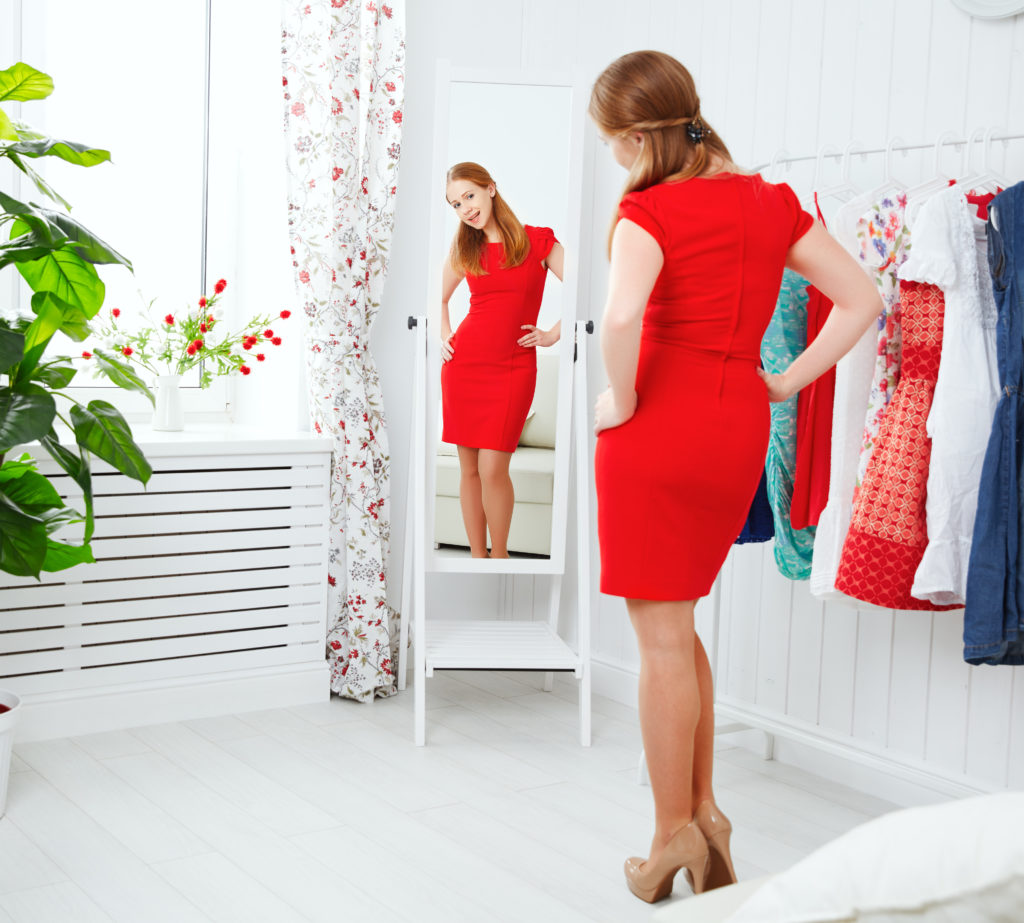 woman in a red dress looks in the mirror and choose clothes
